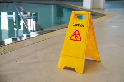 caution wet floor warning sign near swimming pool
